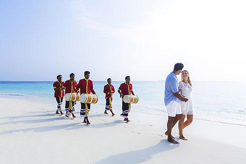 Hochzeitspaar auf den Malediven, begleitet von dem traditionellen Bodu Beru Tanz